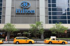 Hilton. NEW YORK - JULY 4: People walk past Hilton hotel at 6th Avenue on July 4, 2013 in New York. Hilton is the 38th largest private company in the United stock images
