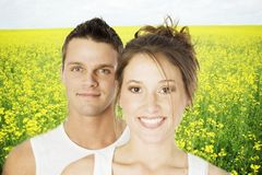 Him and her. Beautiful young couple smiling with a field of canopy in the background stock photos
