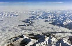 Himalaya mountains under clouds. View from airplane - Tibet Royalty Free Stock Photo