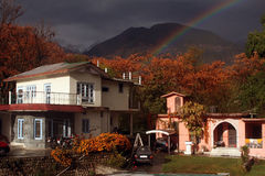 Himalayan cottage homes snow rainbow India Stock Image