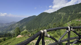 Himalayan Mountain Range with Wooden Railing and Blue sky and Clouds Royalty Free Stock Photography