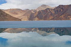 Himalayan mountains. Reflected in the calm blue water of Lake Pangong in Ladakh, Jammu and Kashmir, India Royalty Free Stock Image