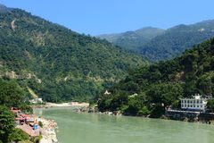 Himalayan mountains and Ganga river on sunny day. Himalayan mountains and Ganga river in sacred town Rishikesh on sunny hot day with clear blue sky Royalty Free Stock Images