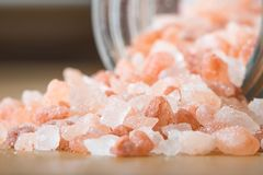 Himalayan pink rock salt in a bottle container on a wooden surface. royalty free stock image
