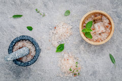 Himalayan pink salt in wooden bowl with peppermint ,sage,thyme,basil and oregano on stone background. Himalayan salt commonly use. D in cooking and for bath royalty free stock photos