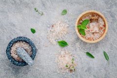 Himalayan pink salt in wooden bowl with peppermint ,sage,thyme,basil and oregano on stone background. Himalayan salt commonly use. D in cooking and for bath stock images
