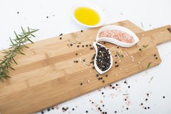 Himalayan Rock Salt, olive oil and peppercorns. Pink Himalayan Rock salt and Peppercorn on a wodden chopping board, set against a white background Stock Photo