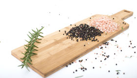 Himalayan Rock Salt, olive oil and peppercorns. Pink Himalayan Rock salt and Peppercorn on a wodden chopping board, set against a white background Royalty Free Stock Images