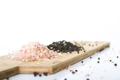 Himalayan Rock Salt. Pink Himalayan Rock salt and Peppercorn on a wooden chopping board, set against a white background Stock Image