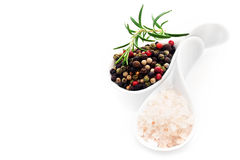 Himalayan salt and black peppercorns. Two white china spoons filled with Himalayan rock salt crystals and black peppercorns with a sprig of fresh rosemary over Royalty Free Stock Image