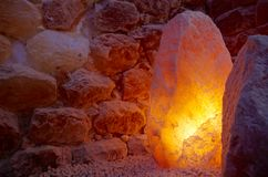Himalayan Salt Lamp and Stones. Himalayan salt lamp and salt stone wall in a halotherapy spa Royalty Free Stock Photo