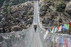 Himalayan sherpa porter on rope bridge. Sherpa porter with cargo on a rope bridge in Nepal Himayas, Valley in Sagarmatha / Everest region, near to Tibet Royalty Free Stock Photography