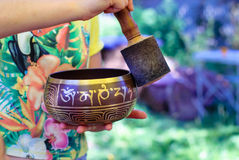 Tibetan singing bowl with Buddhist mantra in man`s hand. Himalayan singing bowl with Buddhist mantra in the person`s hand in the process of sounding Royalty Free Stock Images