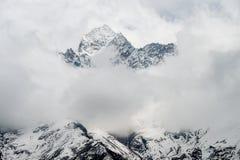 Himalayan toppmöte som dyker upp från molnen Royaltyfria Bilder
