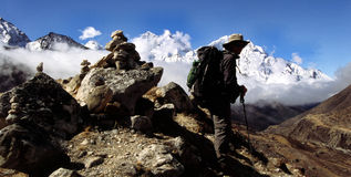 Himalayan trekker. Trekker high in the Himalayas, standing beside a carn with Ama Dablam far in the distance behind him Royalty Free Stock Images