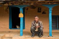 HIMALAYAN VILLAGE, NEPAL - NOVEMBER 25: Unkown man sitting in fron of traditional house of Himalayan Village on November 25, 2014 Royalty Free Stock Photography