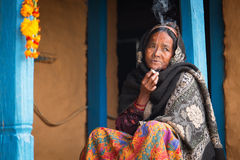 HIMALAYAN VILLAGE, NEPAL - NOVEMBER 25: Unkown woman sitting and smoking in fron of traditional house of Himalayan Village on Nove Royalty Free Stock Images