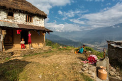 HIMALAYAN VILLAGE, NEPAL - NOVEMBER 25: Unkown woman washing in fron of traditional house of Himalayan Village on November 25. 2014 in HIMALAYAN VILLAGE, Nepal royalty free stock images