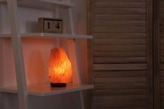 Himalayan zoute lamp op plank stock afbeelding