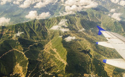 Himalayas aerial view!. Aerial view of the green vegetation covered great Himalayas from the plane. Visible are the treacherous roads and the floating cumulus Royalty Free Stock Images