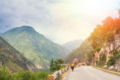 Himalayas landscape with two cyclist, mountains, road, river and clouds Stock Photo