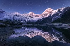 Himalayn mountains and mountain lake at starry night in Nepal. Amazing night scene with himalayan mountains and mountain lake at starry night in Nepal. Landscape Stock Photo