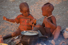 Himba children eating. Himba are an ethnic group of about 20,000 to 50,000 people living in northern Namibia, in the Kunene region (formerly Kaokoland Royalty Free Stock Images