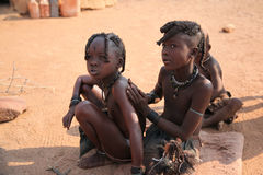 Himba children. In Namibia, in front of the hut, putting clay on their body, as a daily ritual Royalty Free Stock Image
