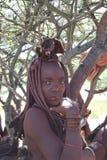 Himba-Frau, die unter dem Baum sich versteckt Lizenzfreie Stockfotografie