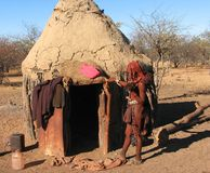 Himba-Frau, die vor Hütte steht stockfotos