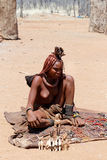 Himba girl with souvenirs for sale in traditional village. NAMIBIA, KAMANJAB, OCTOBER 10: Himba girl with souvenirs for sale in the Himba village in northern stock photo