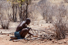 Himba man adjusts wooden souvenirs in fireplace for tourists Royalty Free Stock Images