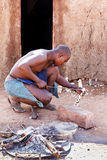 Himba man adjusts wooden souvenirs in fireplace for tourists Stock Image