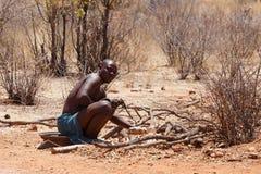 Himba man adjusts wooden souvenirs Stock Photography