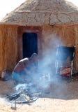 Himba man adjusts wooden souvenirs Stock Photos