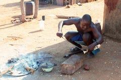 Himba man adjusts wooden souvenirs Stock Images