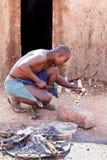 Himba-Mann stellt hölzerne Andenken im Kamin auf Touristen ein Stockbild