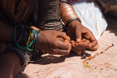 Himba woman making jewelry. Closeup of Himba woman making jewelry Stock Photo