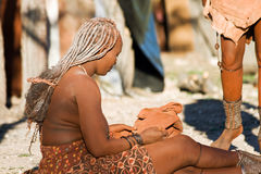 Himba woman sits on the ground. Royalty Free Stock Image