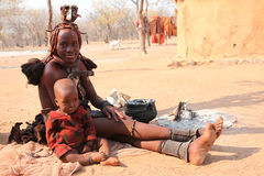 Himba woman and son. In Namibia, in front of the hut Royalty Free Stock Photos