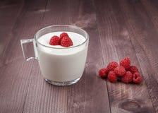 Himbeere auf einer Tabelle und im Glas Jogurt Lizenzfreie Stockfotos