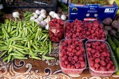 Himbeeren, Knoblauch und Erbsen auf einem Bauernhofmarkt in der Stadt Obst und Gemüse an einem Landwirtsommermarkt lizenzfreie stockfotos