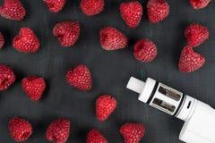 Himbeeren und eine elektronische Zigarette liegen auf einer Dunkelheit Stockbilder