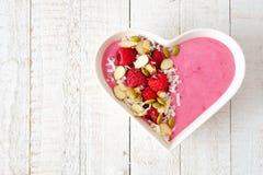 Himbeerensmoothie in einer Herzschüssel mit superfoods über weißem Holz Stockfotografie