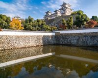 Himeji Castle in autumn reflected in the pond water at the bottom of its fortified walls. The most famous and visited castle in Japan, Himeji Castle is royalty free stock images