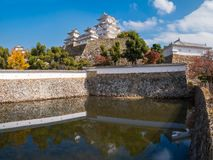 Himeji Castle and fortifications reflected in moat`s water on a beautiful day in autumn in Japan. The most famous and visited castle in Japan, Himeji Castle is royalty free stock images