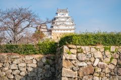 View of Himeji Castle from the fortress stone wall in Japan. Himeji Castle is an iconic 17-th century Japanese castle known for a white facade, plus towers royalty free stock photo