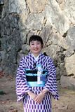 Kind and pleasant of receptionist in Kimono dress on purple and white color at Himeji Castle. stock photo