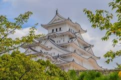 Himeji slott Japan bak träd Arkivbild