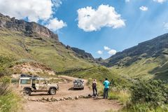Tourists enjoying the view on the Sani Pass. HIMEVILLE, SOUTH AFRICA - MARCH 24, 2018: Two unidentified tourists and four-wheel drive vehicles on the Sani Pass Royalty Free Stock Photos